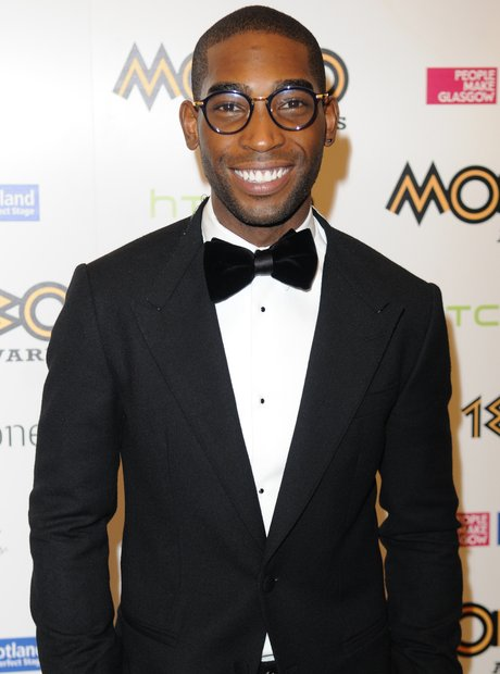 Tinie Tempah wearing suit and smiling at Mobo Awards 2013