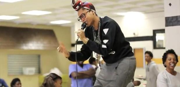 Erykah Badu performing on table in school